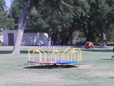 Merry Go Round and outdoor exercise equipment in the back at South Park (Pioneer)